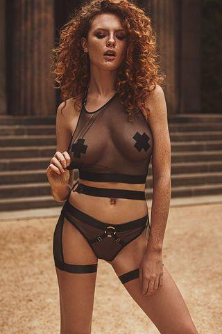 Черный комплект белья Reverie, состоящий из прозрачного топа с открытой спиной, интересного пояса для чулок и трусов-слип, декорированных металлическим кольцом